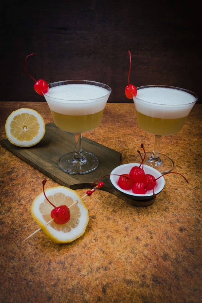 Two whiskey sour mocktails with cherries and lemon