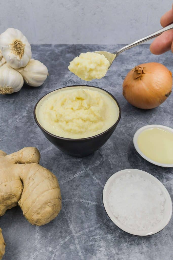 A spoonful of homemade ginger garlic paste with fresh ginger, garlic cloves and onion