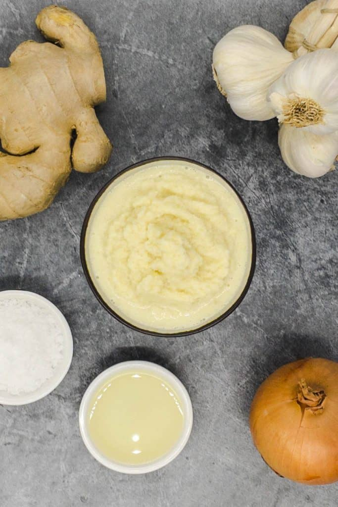Smooth ginger garlic paste with fresh ginger and garlic cloves on grey marble