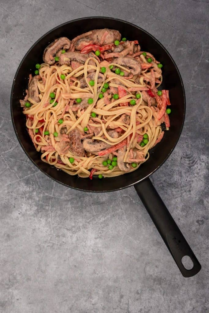 A pan of fantastic tahini pasta with vegan bacon and other veggies