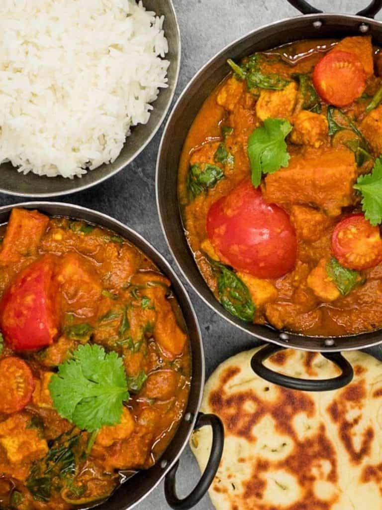 Two bowls of veg bhuna with garnish, rice and naan bread